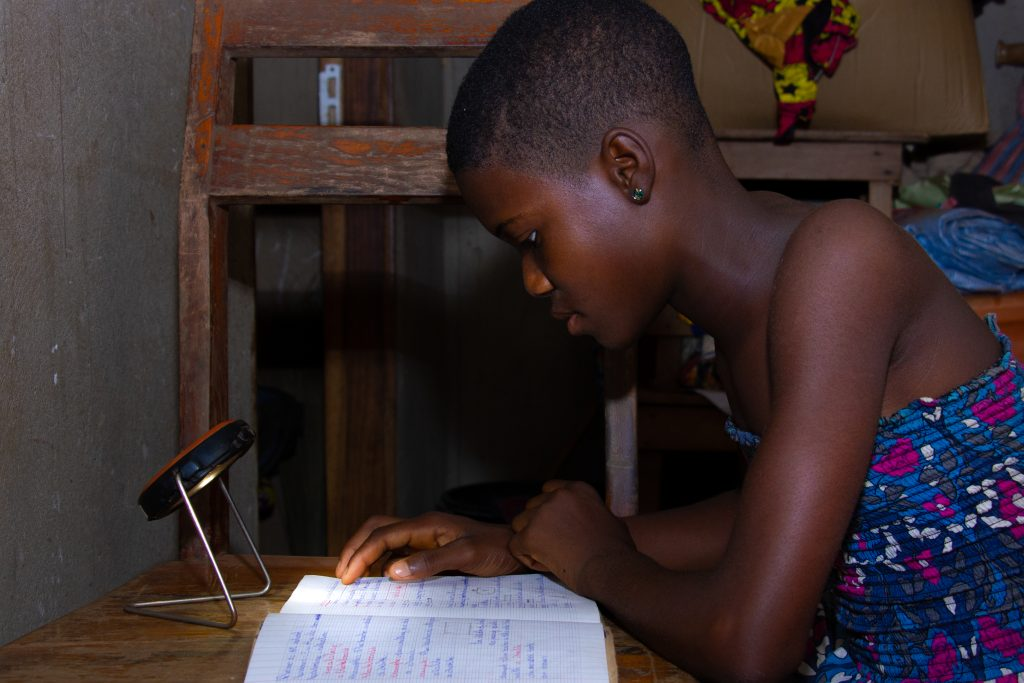 Togolese child using a lamp provided by Deki
